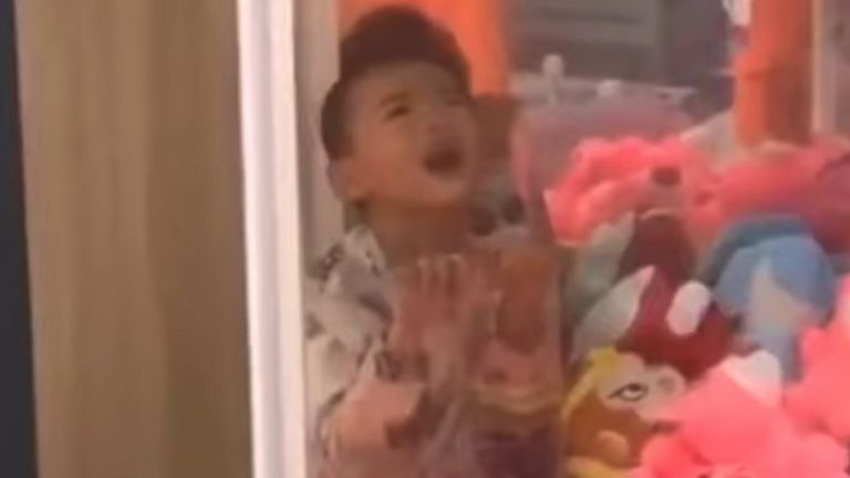 Firefighters were called after a small boy got trapped after crawling into a claw machine in a Chinese shopping centre.