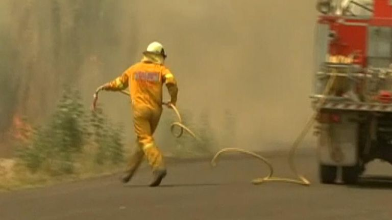A firefighter rushes to contain the spreading inferno