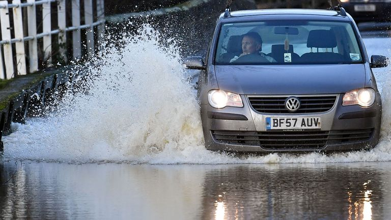 A motorist attempts to drive through a flooded road in Offchurch, Warwickshire