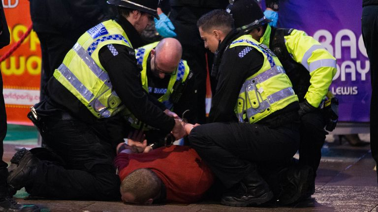 Police make an arrest after a disturbance as revellers in Cardiff make the most of the celebrations on the last Friday before Christmas