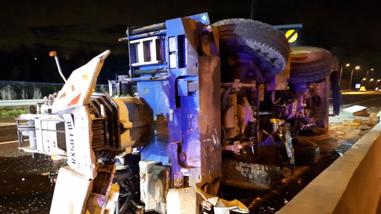 Crane overturned and crashed over both sides of the carriageway of the M25 at Junction 27 with the M11
