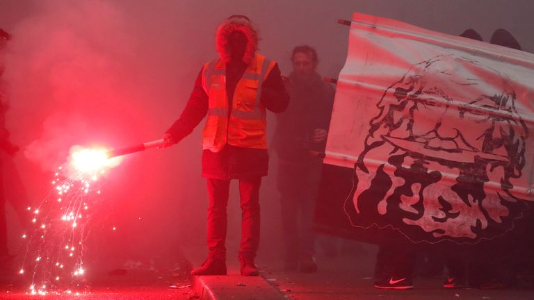 A demonstrator lights a flare