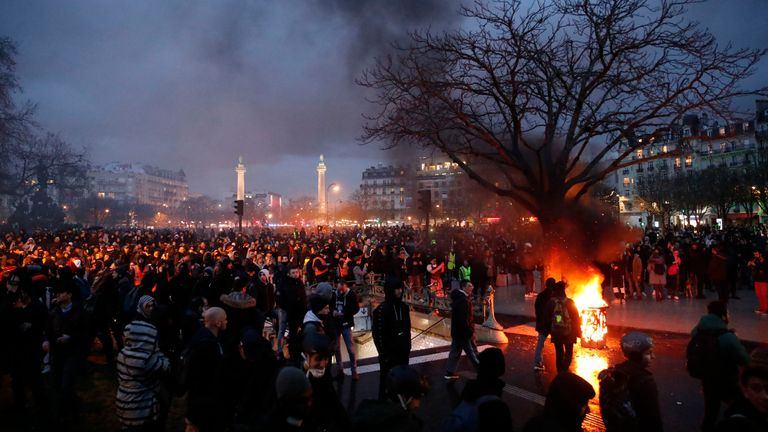 People gather in Place De La Nation as smoke rises from small fires lit at the end of a demonstration in Paris