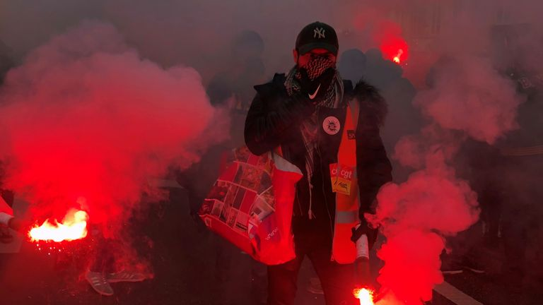 Workers lit red flares and marched beneath union flags through French cities