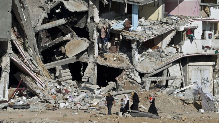 A family in Gaza walks past the remains of a building destroyed in fighting between Hamas and Israel