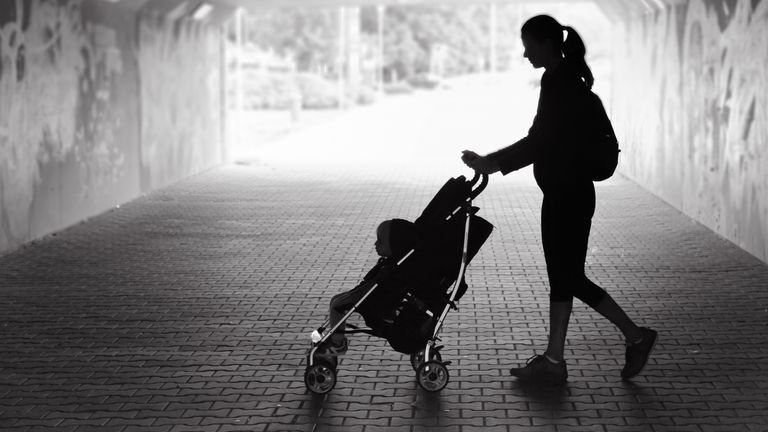 Woman walking with her son in the city stock photo