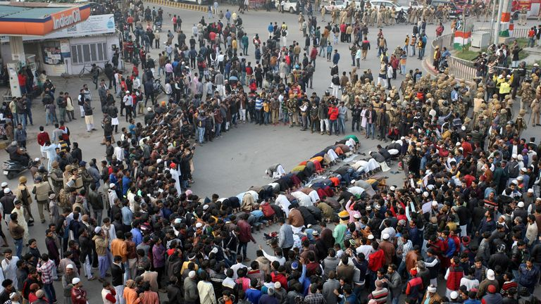 Demonstrators offer prayers on a road during a protest in Allahabad