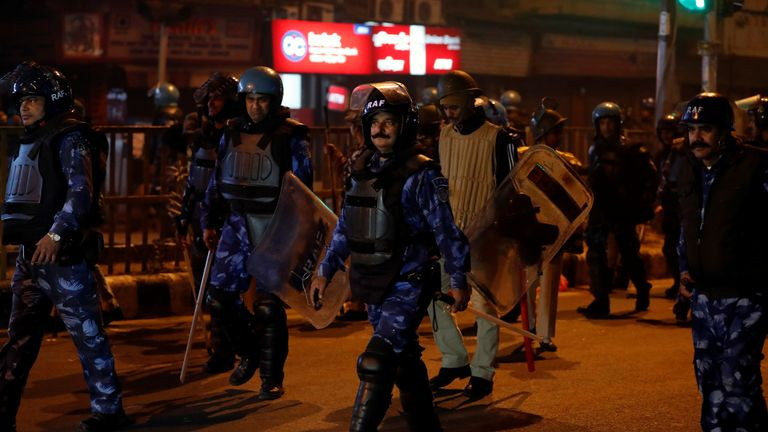 Riot police officers patrol after a protest in Delhi