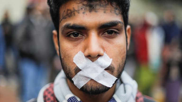 One protester symbolically tapes his mouth shut