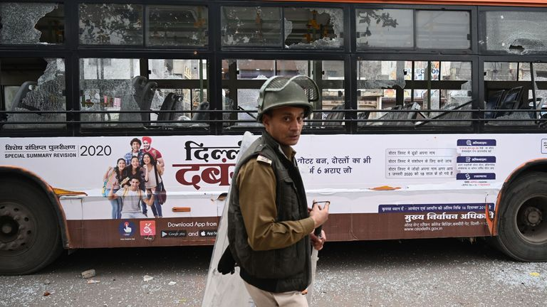 A policeman walks past a bus damaged by protesters