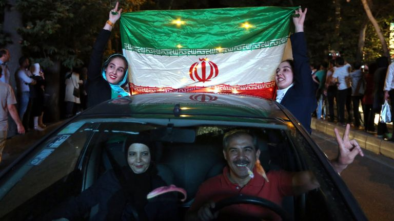 Iranian women wave the national flag while celebrating the deal
