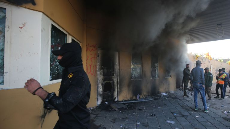 Smoke billows from the entrance of the US embassy in Baghdad after protesters tried to break into the building