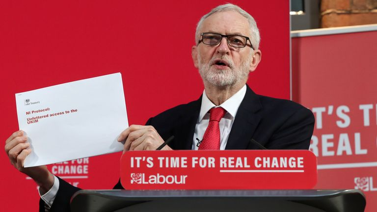 Jeremy Corbyn shows a document during a news conference in London