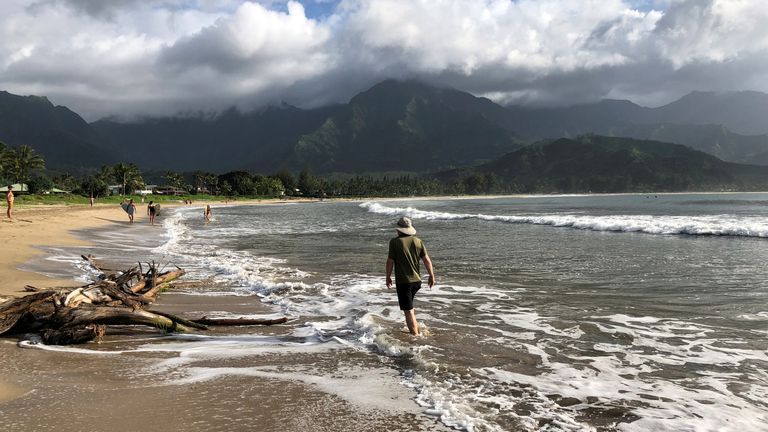 People walk along a calm Hanalei Beach as Hurricane Lane approaches Kauai, Hawaii, U.S., August 22, 2018. REUTERS/Sue Horton