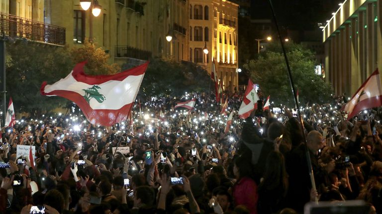 Lebanese demonstrators use their phone lights during an anti-government protest on Sunday