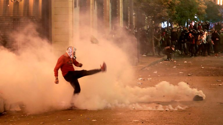 A protester kicks back a tear gas canister during clashes with riot police