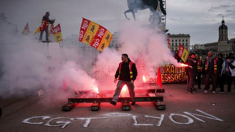 A protester passes by flares during a demonstration in Lyon