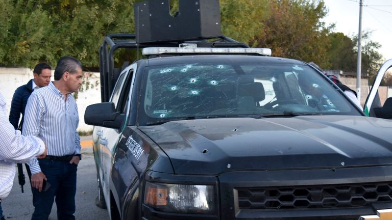 Coahuila state Governor Miguel Riquelme Solis looks at a police vehicle shot during a gunbattle