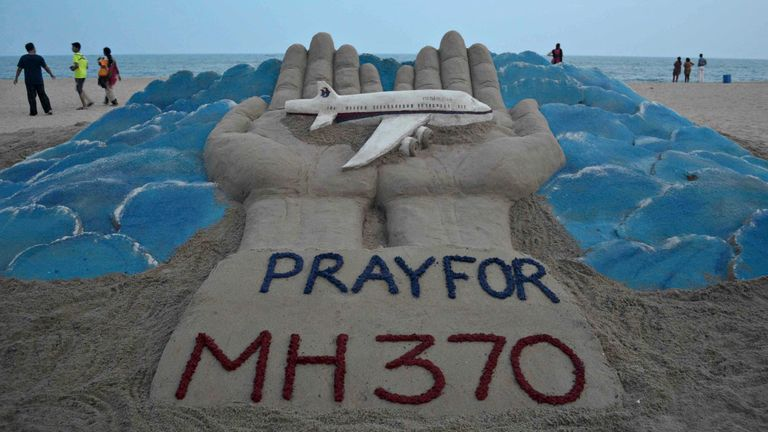 Beachgoers walk past a sand sculpture with a message of prayers for missing flight MH370