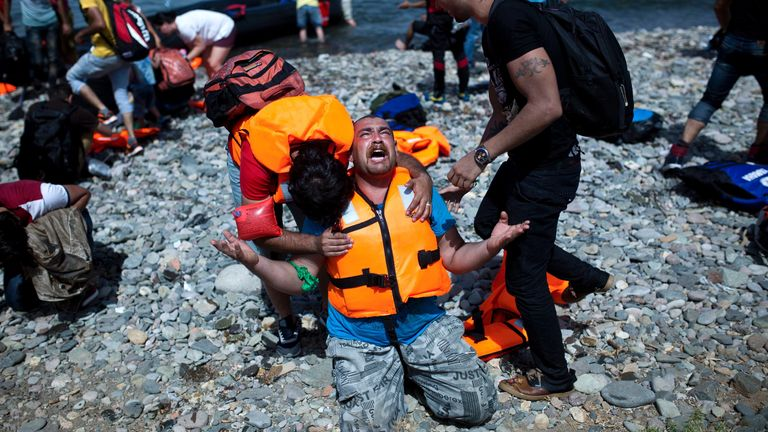 A refugee from Syria prays after arriving on the shores of the Greek island of Lesbos