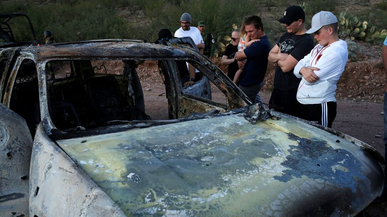 Relatives of slain members of Mexican-American families belonging to Mormon communities observe the burnt wreckage of a vehicle where some of their relatives died, in Bavispe, Sonora state, Mexico November 5, 2019