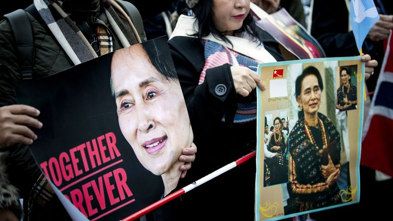 People stand in support of Aung San Suu Kyi on her second day of hearing on the Rohingya genocide case
