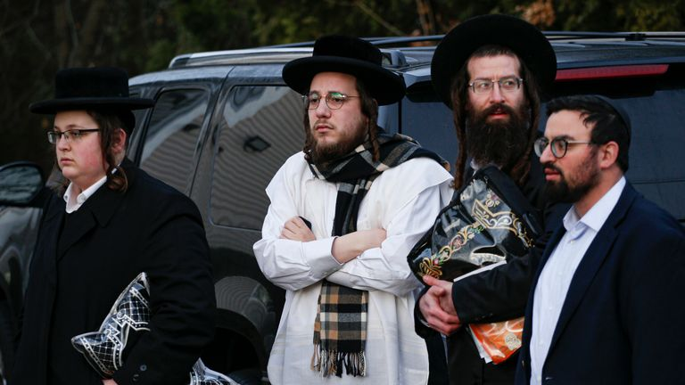 Members of the Jewish community outside the home of a New York rabbi where five people were injured in a knife attack