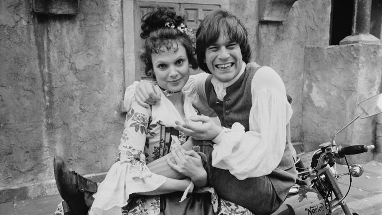British actors Madeline Smith as 'Sophia' and Nicky Henson as 'Tom Jones' on a motorcycle on the set of British comedy film 'The Bawdy Adventures of Tom Jones', UK, 2nd April 1975