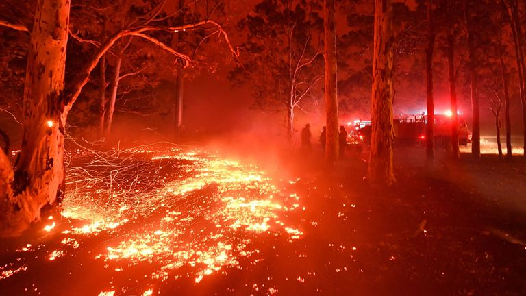 Burning embers cover the ground as firefighters (back R) battle against bushfires around the town of Nowra in the Australian state of New South Wales on December 31, 2019