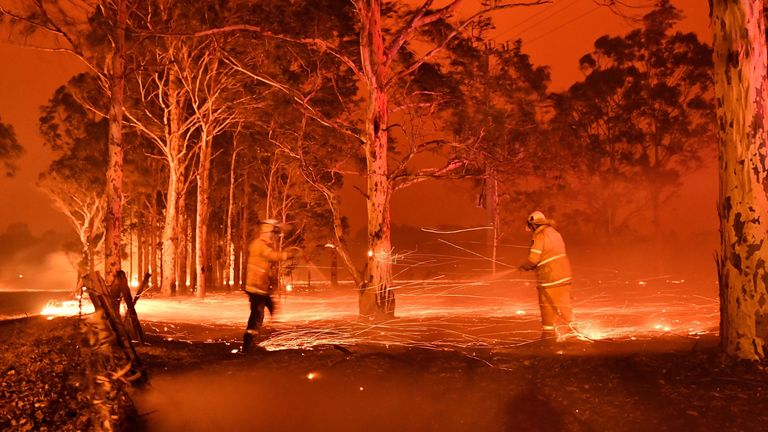 This timed-exposure image shows firefighters hosing down trees as they battle against bushfires around the town of Nowra in the Australian state of New South Wales on December 31, 2019
