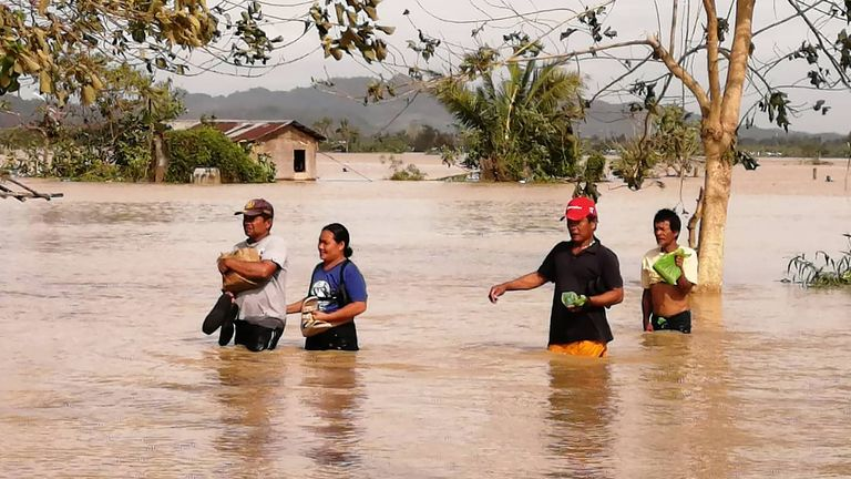 Residents wade through a flooded highway, caused by heavy rains due to typhoon Phanfone, in Ormoc City, Leyte province 25 december