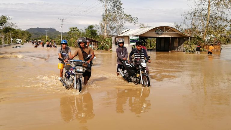 Motorists wade through a flooded highway, caused by heavy rains due to typhoon Phanfone, in Ormoc City, Leyte province in central Philippines