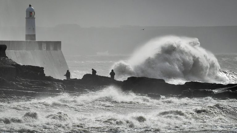 Huge waves slap against the harbour wall