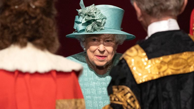 The Queen talks with officials following her speech to Parliament on the day of the  state opening of parliament.