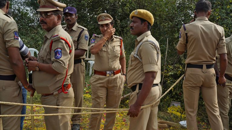 Police officers stand at the site where police shot dead four men suspected of raping and killing a 27-year-old vet