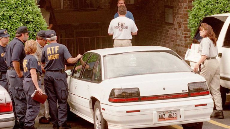 US Federal agents gather 31 July outside the home of Richard Jewell, the security guard who was working at Centennial Park at the time of the 27 July pipe bomb explosion. Federal authorities reportedly searched the apartment for evidence that might link Jewell to the bombing