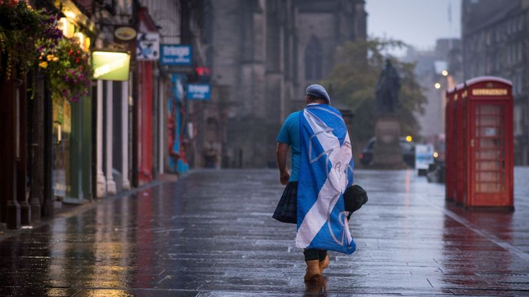 A dejected 'Yes' supporter in Edinburgh makes his way home in the early hours after Scotland voted decisively to reject independence and remain part of the Union
