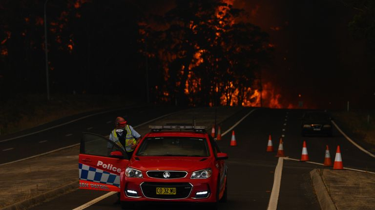 A New South Wales Police officer prepares to flee his roadblock on the Princes Highway near the town of Sussex Inlet on December 31, 2019 in Sydney, Australia