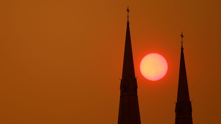 The sun sets behind St Mary's Cathedral in Sydney on 6 December 2019. Most of NSW remains under severe or very high fire danger warnings as more than 50 fires continue to burn across the state