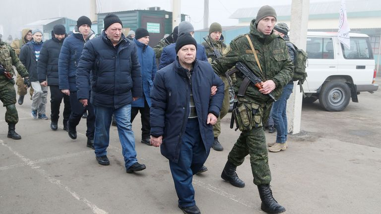 Men are escorted by servicemen of the self-proclaimed republics during the exchange of prisoners of war (POWs) between Ukraine and the separatist republics near the Mayorsk crossing point in Donetsk region, Ukraine