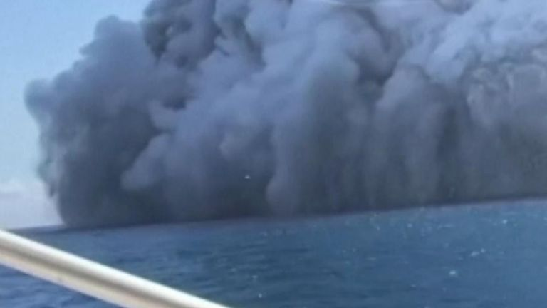Tourists captured a plume of ash rising in the sky as their boat sails away from an erupting volcano on New Zealand's White Island