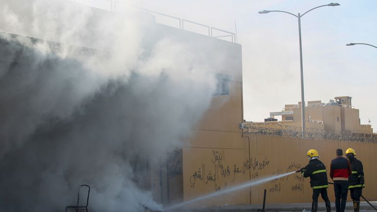 "A firefighter extinguishes a flame on the entrance of the US embassy in the Iraqi capital Baghdad on January 1, 2020 during a demonstration by supporters and members of the Hashed al-Shaabi paramilitary force. - Thousands of Iraqi supporters of the largely Iranian-trained Hashed al-Shaabi paramilitary force had gathered at the embassy, outraged by US strikes that killed 25 Hashed fighters over the weekend. They marched unimpeded through the checkpoints of the usually high-security Green Zone to the embassy gates, where they broke through a reception area, chanting ""Death to America"" and scribbling pro-Iran graffiti on the walls. (Photo by AHMAD AL-RUBAYE / AFP) (Photo by AHMAD AL-RUBAYE/AFP via Getty Images)"