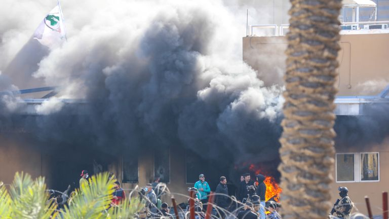 Attackers and assailants set fire to a gate as smoke rises from inside the compound of the U.S. embassy in Baghdad, Iraq January 1, 2020.  U.S. Army/Staff Sgt. Desmond Cassell/Task Force-Iraq Public Affairs/Handout via REUTERS.  THIS IMAGE HAS BEEN SUPPLIED BY A THIRD PARTY.
