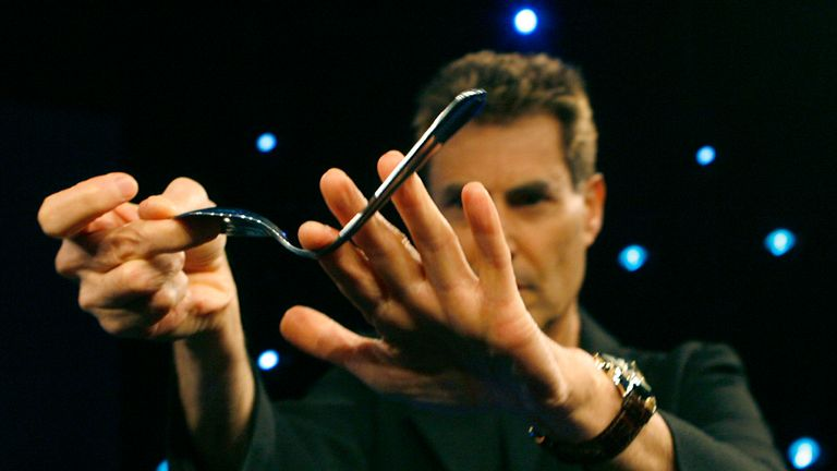 Israeli psychic Uri Geller bends a spoon during a photographers call in Cologne January 6, 2008. The famed 'spoon-bender' Geller, who burst on the world scene in the 1970s with telekinetic performances starts a new television show 'The next Uri Geller' in Germany on January 8, 2008.  REUTERS/Ina Fassbender  (GERMANY)