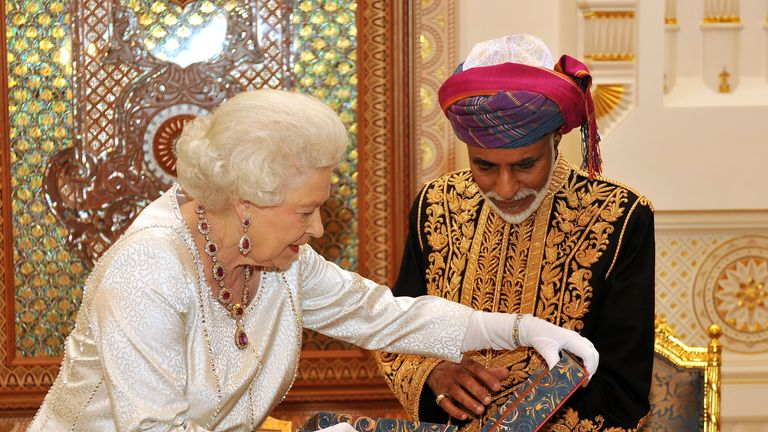 MUSCAT, OMAN - NOVEMBER 26:  Queen Elizabeth II presents the Sultan of Oman, His Majesty Sultan Qaboos bin Said with a book, before a State Banquet at his Palace  on November 26, 2010 in Muscat, Oman. The Queen and Duke of Edinburgh formally begins the second leg of her Gulf state visit. The Royal couple have spent two days in Abu Dhabi and will spend three days in Oman. (Photo by John Stillwell -  Pool/Getty Images)