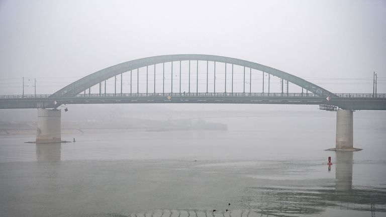 A pedestrian walks over a bridge in Belgrade, stretching over the Sava river, as heavy fog and air pollution dominate the sky over the Serbian capital Belgrade on January 16, 2020. - A thick cloud of pollution has been visible over the city for several days now, and according to the AirVisual app, Belgrade has several times in the last week been among the most polluted cities in the world. (Photo by Andrej ISAKOVIC / AFP) (Photo by ANDREJ ISAKOVIC/AFP via Getty Images)