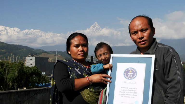 Nepalese Khagendra Thapa Magar (C), the world's smallest man, poses with his parents Rup Bahadur Thapa Magar (R) and mother Dhana Maya Thapa (L) while holding his Guiness record certificate against the backdrop of Mount Machchhapuchhre at their home in Pokhara, some 200 kms west of Kathmandu, on October 29, 2010. Magar was officially recognised as the world's shortest man by the Guinness Book of World Records on October 14, 2010 when he turned 18. Khagendra Thapa Magar stands just 26.4 inches (67.08 centimetres) tall, according to final measurements taken by Guinness World Records. AFP PHOTO/Prakash MATHEMA (Photo credit should read PRAKASH MATHEMA/AFP via Getty Images)
