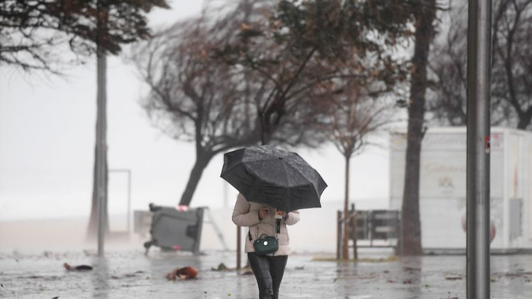 A woman walks with difficulty due to the strong wind in El Bogatell beach in Barcelona as storm Gloria batters Spanish eastern coast on January 21, 2020. - Freezing winds, heavy snow and rain lashed parts of Spain yesterday, killing three people, forcing the closure of schools that cancelled classes for nearly 200,000 students and disrupting travel, officials said. (Photo by Josep LAGO / AFP) (Photo by JOSEP LAGO/AFP via Getty Images)