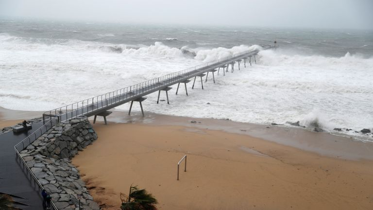 "A man (L) takes a pictures of the Petroleum (Petroleo) bridge during the storm ""Gloria"" on Maresme coast in Badalona, near Barcelona, Spain, January 21, 2020. REUTERS/Nacho Doce"