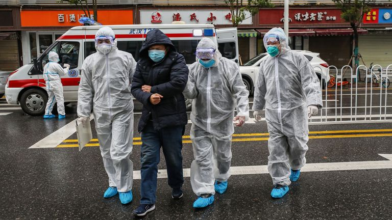 TOPSHOT - This photo taken on January 26, 2020 shows medical staff members wearing protective clothing to help stop the spread of a deadly virus which began in the city, accompanying a patient (2nd L) as they walk into a hospital in Wuhan in China's central Hubei province. - China on January 27 extended its biggest national holiday to buy time in the fight against a viral epidemic, as the death toll spiked to 81 despite unprecedented quarantine measures and travel lockdowns. (Photo by STR / AFP) / China OUT (Photo by STR/AFP via Getty Images)